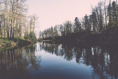Scenic reflections of trees and clouds in water - retro vintage Royalty Free Stock Photography