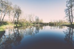 Scenic reflections of trees and clouds in water - retro vintage Royalty Free Stock Images
