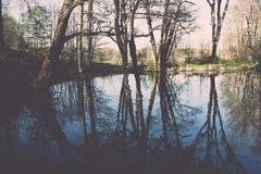 Scenic reflections of trees and clouds in water - retro vintage Royalty Free Stock Photos
