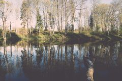 Scenic reflections of trees and clouds in water - retro vintage Royalty Free Stock Photo