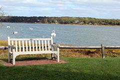 Scenic bench. Wood bench in seaside park with view of boats on the water Stock Photos