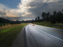 Scenic Black Hills Sunset with winding roads and motorcyclists. Motorcyclists on a curving road near Lead, South Dakota on a stormy evening near sunset, the stock photography