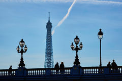 Scenic cityscape of Paris with silhouettes of people and Eiffel tower. Scenic cityscape of Paris with silhouettes of people and lanterns on the famous Alexandre Stock Image