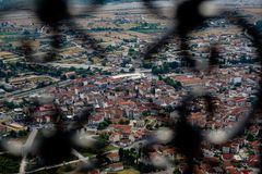 Scenic cityscape view of ancient red roof buildings, urban street and space in Kalambaka from Meteora monasteries rock. Through wrought iron rail blurred stock images