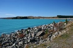 Scenic coast with astonishing milky azure blue water, distant trees and mountains. Landscape on deep turquoise color Lake Pukaki, Canterbury, South Island, New royalty free stock photo