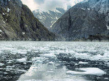 Scenic coastal landscape with steep glacially polished cliffs and floating ice at Tracy Arm Fjord Stock Image