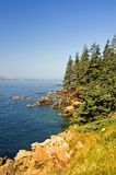 Scenic coastline of Maine. A view of the beautiful rocky coastline of Maine  with blue water and sky on Swans Island on a clear, summer day Royalty Free Stock Photography