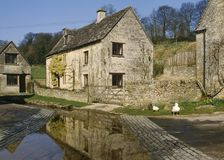 Scenic Cotswolds - Duntisbourne Leer. Cotswold stone cottages by the old ford in spring sunshine,  Duntisbourne Leer, Cotswolds, Gloucestershire, UK Royalty Free Stock Photography