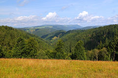 Scenic countryside landscape in the Black Forest: green summer mountain valley with forests, fields and old houses in Royalty Free Stock Image