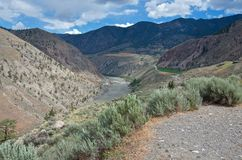 Scenic desert canyon of muddy Fraser river in cloudy weather in summer stock photos