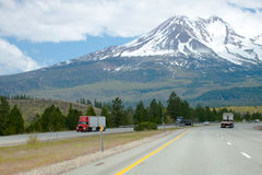 Scenic divided highway with semi trucks and snow mountain Royalty Free Stock Photography