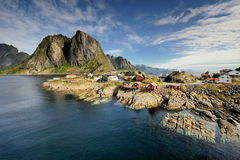 Scenic fjord on Lofoten islands with typical red fishing hut and towering mountain peaks Stock Photos