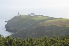 Scenic green cape with lighthouse royalty free stock photography