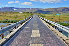 Scenic Icelandic road for cars with green mountains in the background Stock Images