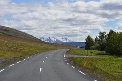 Scenic Icelandic road for cars with green mountains in the background Stock Photography