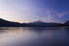 Scenic italian lake. A peacuful lake at sunset with calm water and the mountains on the background Stock Photography