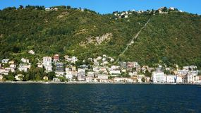 A scenic Italian village at bank of big mountain lake in summertime.  stock image