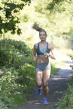 Scenic jog route. Young woman running along a woodland path Stock Images