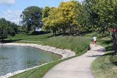 Scenic jogging path with runner. Scenic biking/jogging trail with runner in central Iowa Stock Images