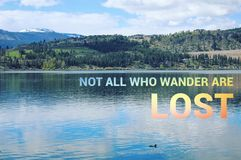 Conceptual lake landscape with duck in water. Scenic lake landscape with duck swimming in calm water and colorful text. Not all who wander are lost Royalty Free Stock Images