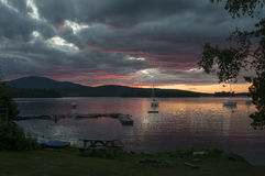 Scenic lake sunset over mountains. Glowing sunset in clouds over a mountain lake.  Moosehead Lake, Greenville, Maine Royalty Free Stock Photos