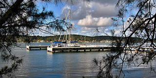 Scenic Lake Wharf. `F` Jetty - Wharf at Lake Macquarie with trees in the foreground and a blue cloudy sky. New South Wales, Australia Stock Images