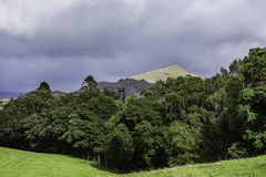 Scenic landscape of british countryside in rural area of Lake District,Cumbria,Uk. Trees growing on hilly grass field and sky with rain clouds above mountain top stock photos