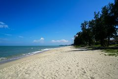 Scenic landscape of calm sea wave on white sandy beach with green tree line shade and clear blue sky background. Samila beach, Songkhla, Thailand Stock Photos