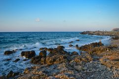 Rocks and waves with the nice blue sky in Crete, Greece. Scenic landscape with the coast, the rocks, the beautiful sea and the blue sky in Crete Royalty Free Stock Photo