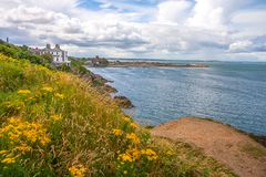 Scenic landscape Howth coastal walk, Ireland. Panoramic view of Howth coastal town and Howth lighthouse, Dublin Bay, Ireland Royalty Free Stock Photography