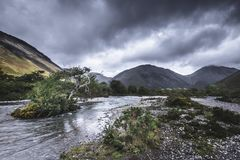 Scenic landscape of Lake District,Cumbria,Uk. Small island with tree on the middle of  stream flowing in beautiful  valley and moody sky with dark clouds stock photography
