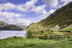 Scenic landscape of Lake District,Cumbria,Uk. Lake in scenic valley and mountain slope with cloudy sky above.Idyllic landscape of Cumbria in North West England stock photography