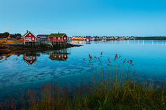 Scenic landscape on Lofoten islands with typical red fishing hut and towering mountain peaks. Amazing view of Lofoten islands: village Reine with red houses near Royalty Free Stock Image
