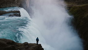 Scenic landscape of the lonely man standing on the edge of the mountain and looking on the Gullfoss waterfall in Iceland stock video footage