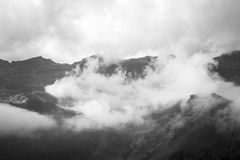 Scenic landscape mountain photography. Black and white photography full of mood view of the Strona valley in the italian alps cover by clouds illuminated by royalty free stock images