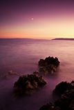 Scenic landscape and the ocean. Beautiful landscape of an islands and ocean with sunlit red sky and a young moon Stock Images