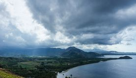 Scenic landscape Picture of land and sea on the deep village in Flores islands during the cloudy and windy day with sun rays goes stock images