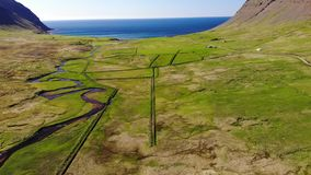 Scenic landscape, rivers, meadows, sea, near Bolungarvik, Iceland. Rvier meandering to the sea through green fields, near Bolungarvik, Iceland stock video footage