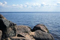 Scenic landscape with sandy shore, boulders, sea and sky. Atmospheric view stock photos