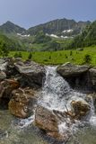 Scenic landscape of snowy mountain in the background and a small waterfall in the foreground Royalty Free Stock Photography