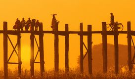 Scenic landscape of U Bein bridge at sunset with silhouettes of people.Suburbs of Mandalay, Myanmar royalty free stock photography