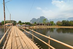 Scenic landscape in Vang Vieng, Laos at day. Limestone mountains, wooden bridge, empty waterfront restaurant, bungalows and Nam Song River in Vang Vieng stock image