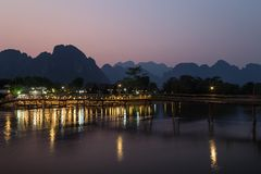 Scenic landscape in Vang Vieng, Laos at dusk. Silhouette of a karst limestone mountains, bridge and few people at a lit waterfront restaurant by the the Nam Song stock images