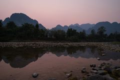 Scenic landscape in Vang Vieng, Laos at dusk. Silhouette of a karst limestone mountains and their reflections on the Nam Song River in Vang Vieng, Vientiane royalty free stock photo