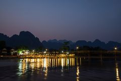 Scenic landscape in Vang Vieng, Laos at dusk. Silhouette of limestone mountains, wooden bridge, people at a lit waterfront restaurant and reflections on the Nam stock photography