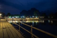 Scenic landscape in Vang Vieng, Laos at night. Lit wooden bridge and reflections of a waterfront restaurant by the the Nam Song River in Vang Vieng, Vientiane stock photo
