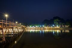 Scenic landscape in Vang Vieng, Laos at night. Reflections of lit wooden bridge and waterfront restaurant by the the Nam Song River in Vang Vieng, Vientiane stock photos