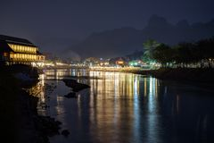 Scenic landscape in Vang Vieng, Laos at night. Silhouette of karst limestone mountains and reflections of lit waterfront restaurants by the the Nam Song River in stock photo