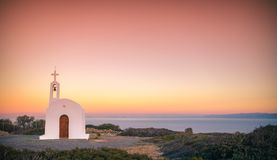 Scenic landscape with a white church and aegean sea at sunset, Crete. Stock Images
