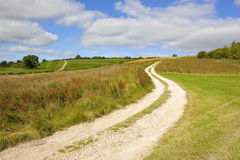 Scenic limestone bridleway in summertime. A limestone country bridleway going through an area used for clay pigeon shooting tournaments under a blue cloudy sky Stock Images